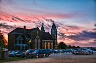 event takes place at the church grounds, cars parked in lot as sun sets Friday night