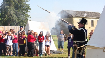 Part of the Ghost Garrison, Greg Emery of Des Moines demostrates the 1777 black powder muskat for a group of students from Waterloo Schools.