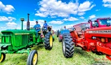 Getting in line in a field for the parade on the John Deere 3020 driving the youth float is Austin & Dan Schutte.